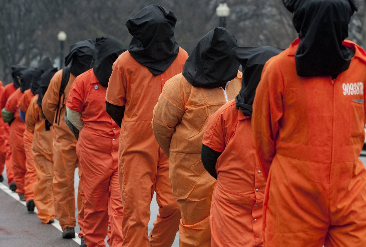 Protesters wearing orange prison jump suits and black hoods march during a protest against holding detainees at the military