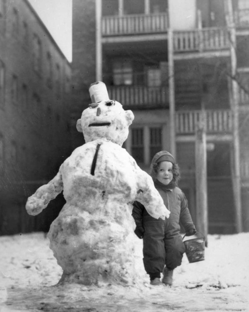 """A little Chicago girl poses with the snowman she made, circa 1944. <em>Photo courtesy the <a href=""""http://chicagohistorymuse"""