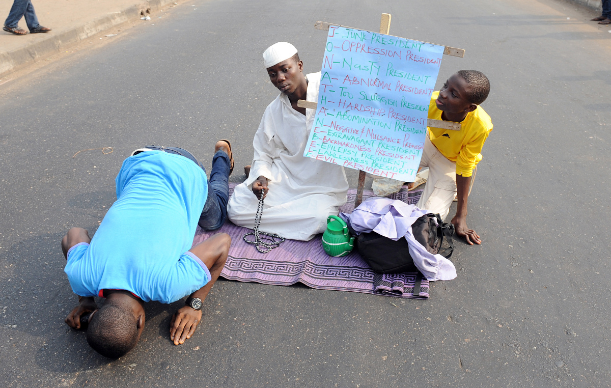Muslim faithfuls carry placard and pray on Lagos - Ikorodu highway on the fourth day of protest against the scrapping of oil