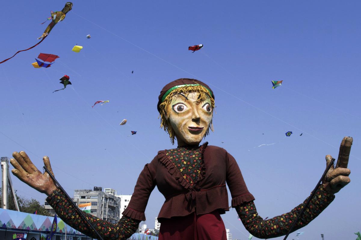 A giant puppet stands as kites fly during the International Kite Festival in Ahmadabad, India, Wednesday, Jan. 11, 2012. More