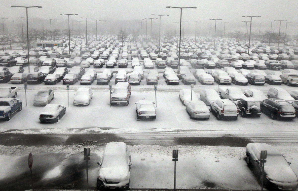 Snow covers cars at an O'Hare International Airport parking lot in Chicago on Thursday, Jan. 12, 2012. The season's first maj