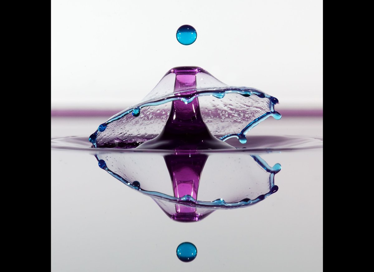 A stem of purple water shoots into the air as a blue droplet cascades around it.
