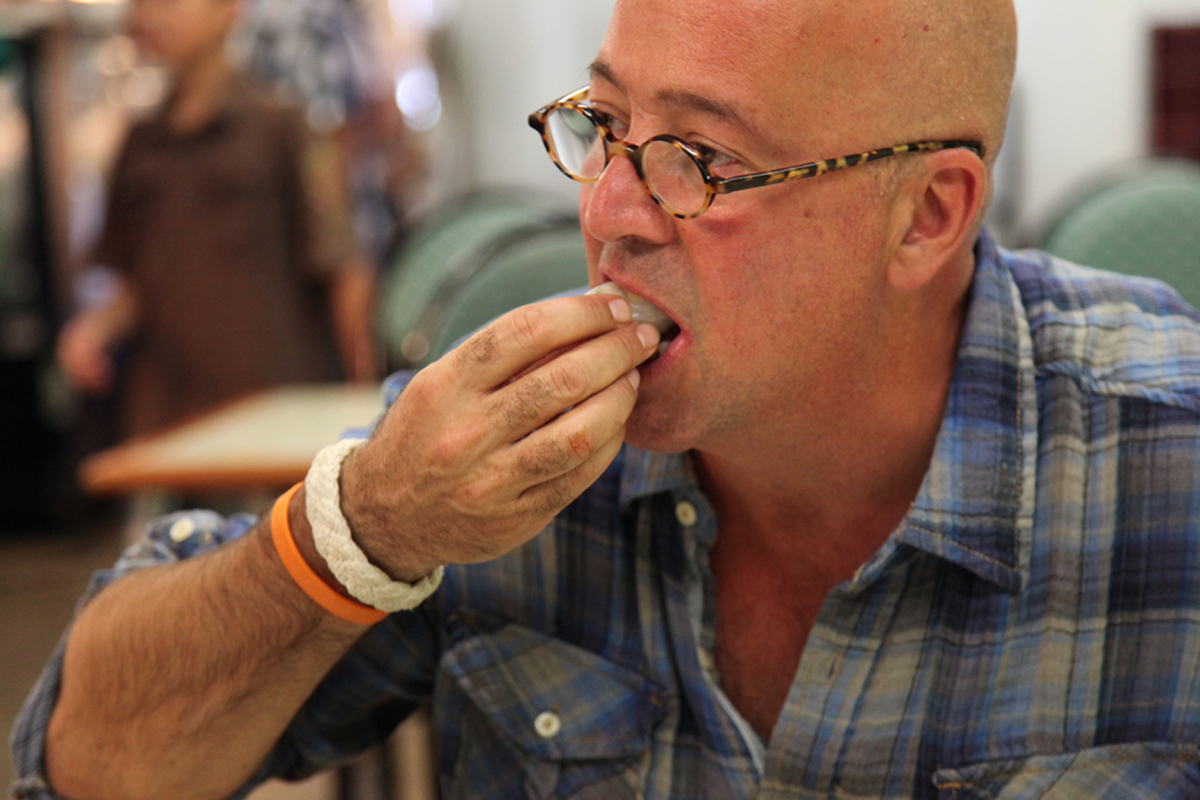 """Zimmern tries a spring roll from <a href=""""http://www.hmongtownmarketplace.com/about.html"""" target=""""_hplink"""">Hmongtown Market</"""
