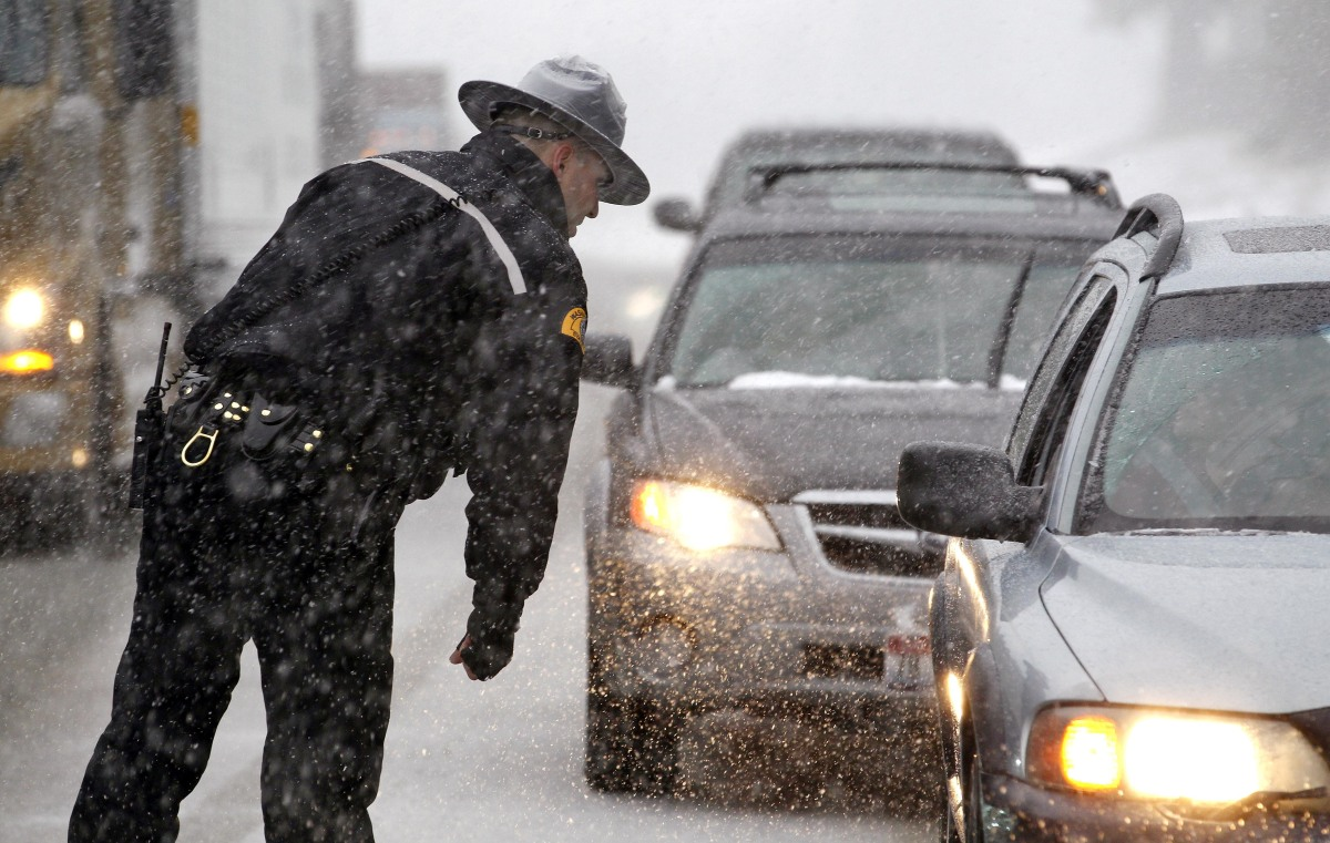 <em>From AP:</em> Washington State Patrol trooper Josh Griffith stands in a heavy snow fall as he talks with drivers on Inter