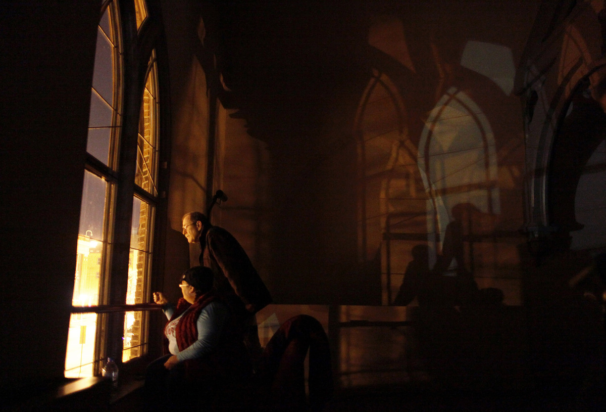Jeff Jerome, top left, curator of the Poe House and Museum, and Jeannette Marxen stand watch at a window in Westminster Hall,