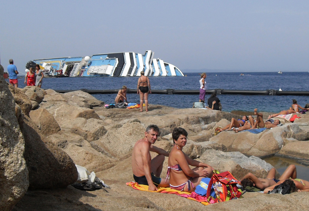 In this image taken Saturday, Aug. 11, 2012, sunbathers sit in front of the wreck of Costa Concordia outside the port of Isol
