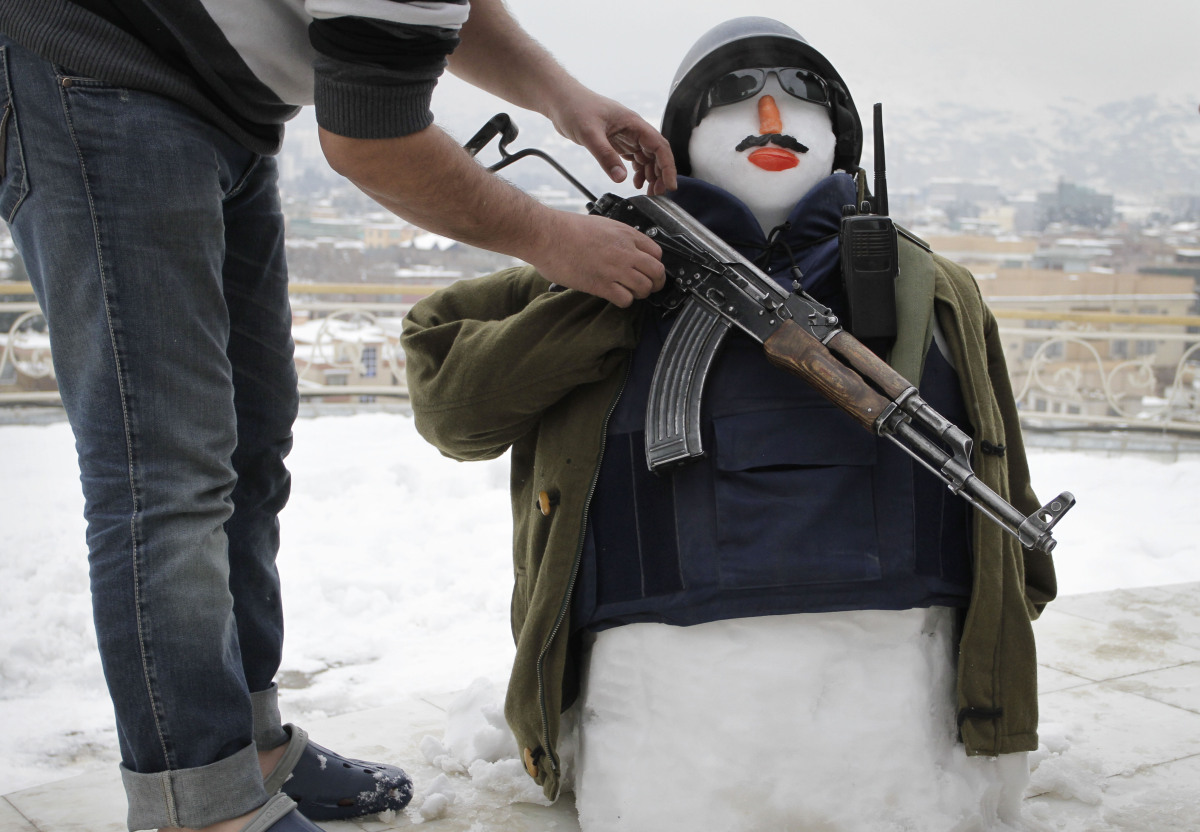 An Afghan man makes a snowman outfitted with body armor and a weapon after a snowstorm in Kabul, Afghanistan, Sunday, Jan, 15