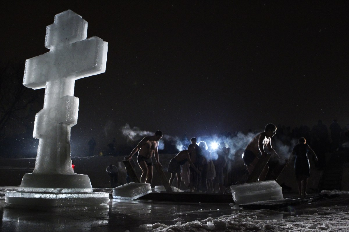 People gather around a bath of ice cold water as they prepare to plunge into it at the Kolomenskoe park on the outskirts of M