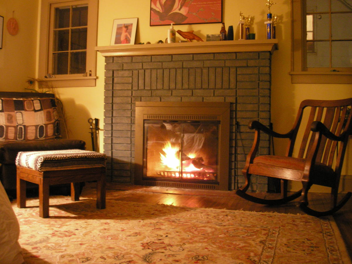 There's nothing cozier than the combination of a warm color scheme and a roaring fire. The yellow tinted walls, wooden accent