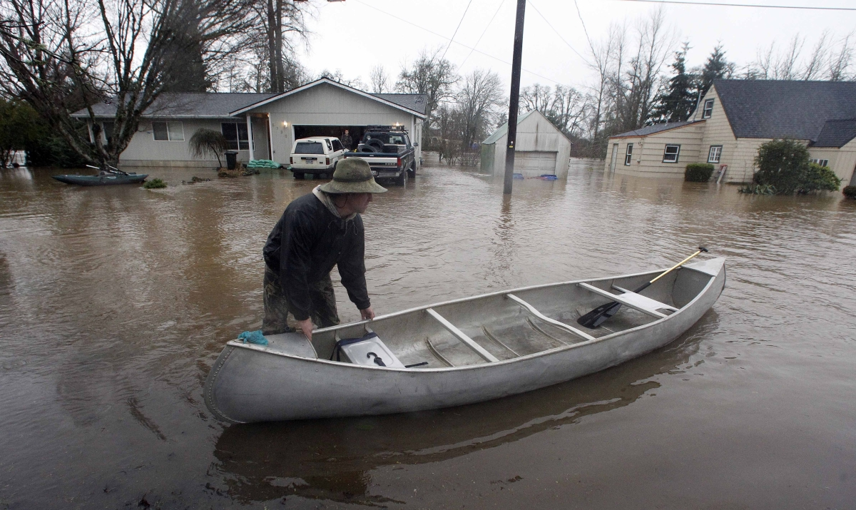 <em>From AP:</em> Esa Korkeakoski pulls his canoe through the swollen Mill Creek Thursday, Jan. 19, 2012, in Turner, Ore. Up