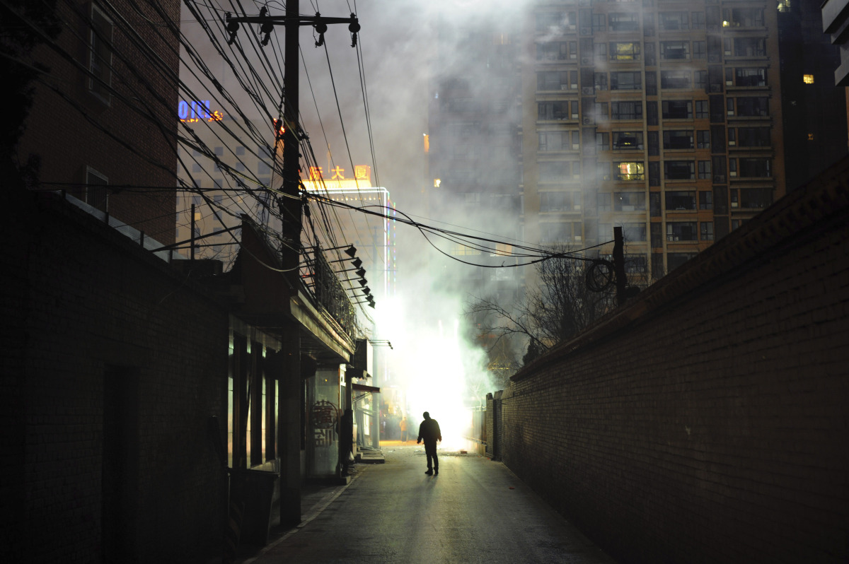 A man watches fireworks explode in an alleyway in Beijing on January 22, 2012. China is welcoming the year of the dragon, a s