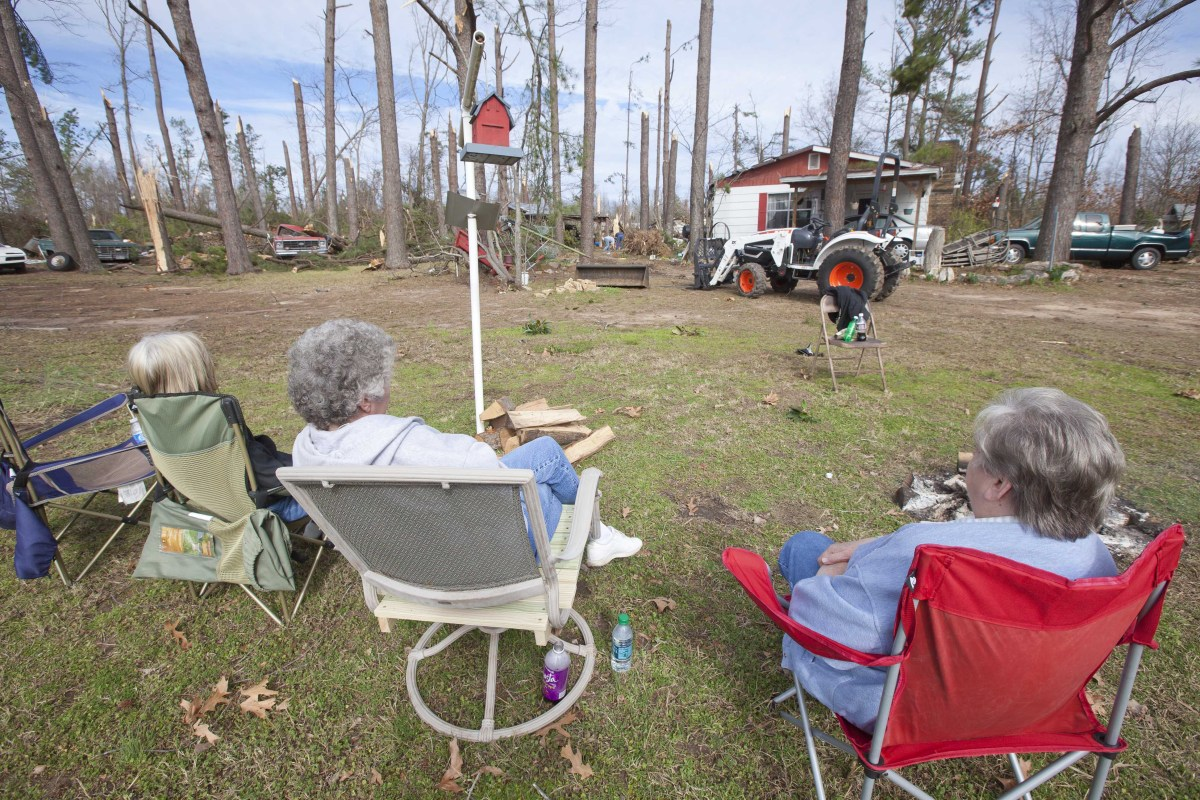 <em>From AP:</em> Three women sit in lawn chairs in a storm-damaged neighborhood in Fordyce, Ark., Monday, Jan. 23, 2012. The