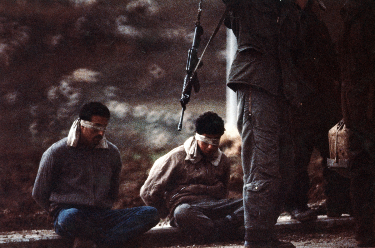 Palestinian prisoners being taken in for questioning in the West Bank, during the Israeli-Palestinian conflict, 1989.  (James