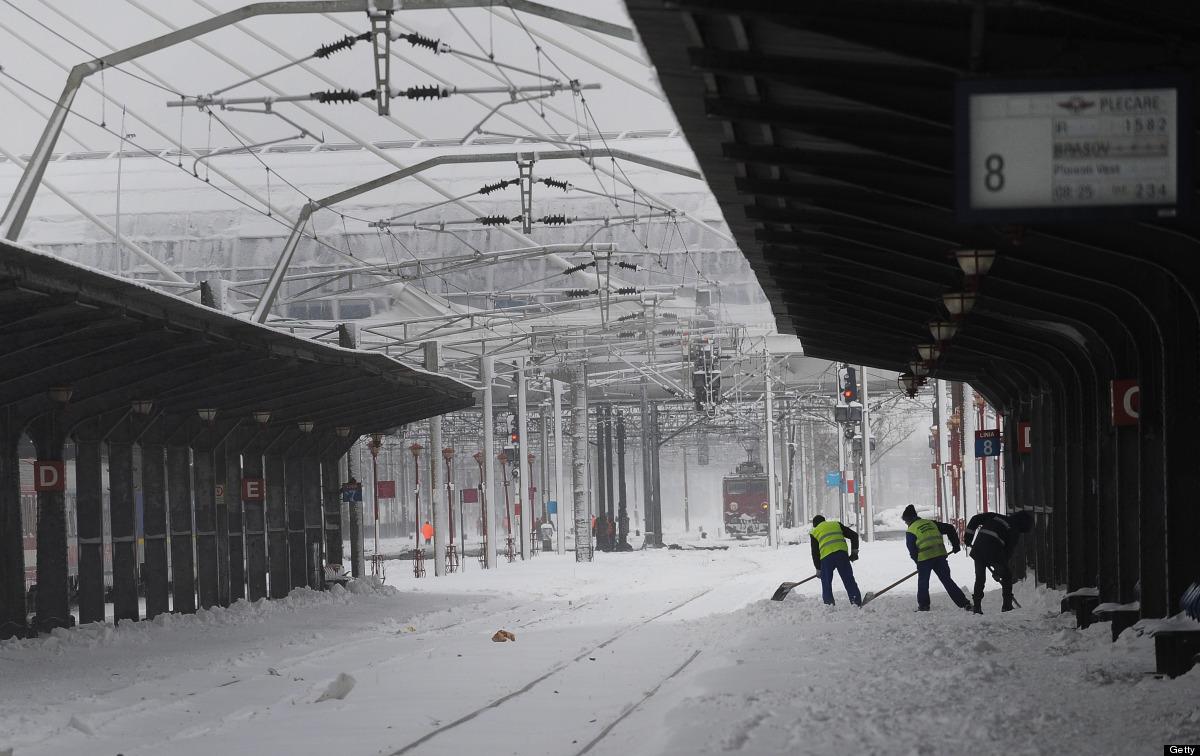 Romanian Railway Company (CFR) employees clear snow in the Gara de Nord railway station in Bucharest on January 26, 2012. Pri