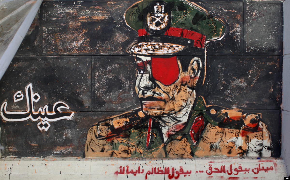 """Graffiti depicting a high ranking army officer with an eye patch and Arabic writing that reads, """"your eye, the square says th"""