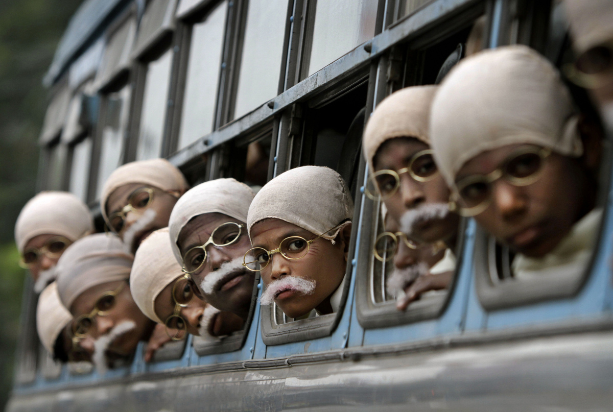 Underprivileged Indian children dressed in costume to look like the late Mahatma Gandhi arrive on a bus before attempting a w