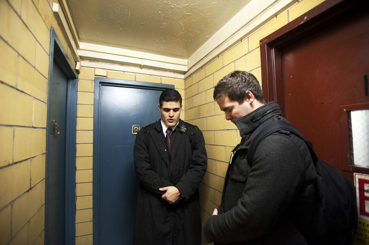 Mormon missionaries, Elder Merrill and Elder Irizarry pray before the knock on doors at an apartment building in Chelsea. The