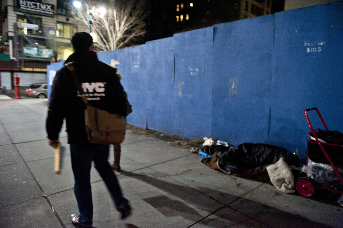 Volunteers along with members of the New York City Department of Homeless Services walk by a homeless person sleeping on the