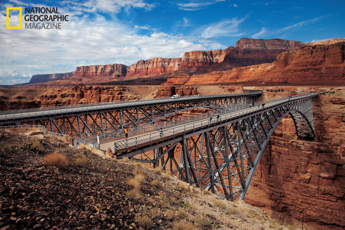 Against the soaring backdrop of Arizona's Vermilion Cliffs, the 1929 Navajo Bridge, now used for foot traffic, crosses the Co