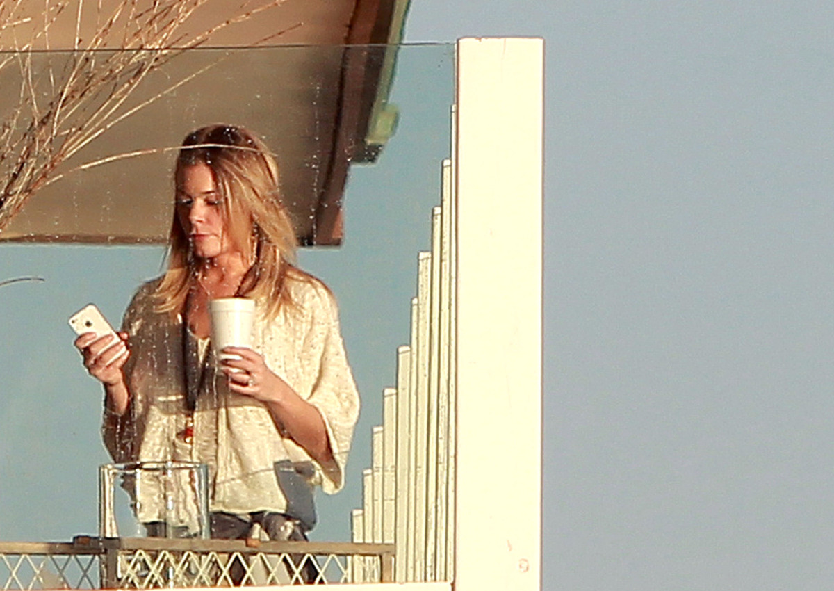 LeAnn Rimes wears her standard tiny bikini as she hangs out on a beach front balcony with her husband Eddie Cibrian and frien