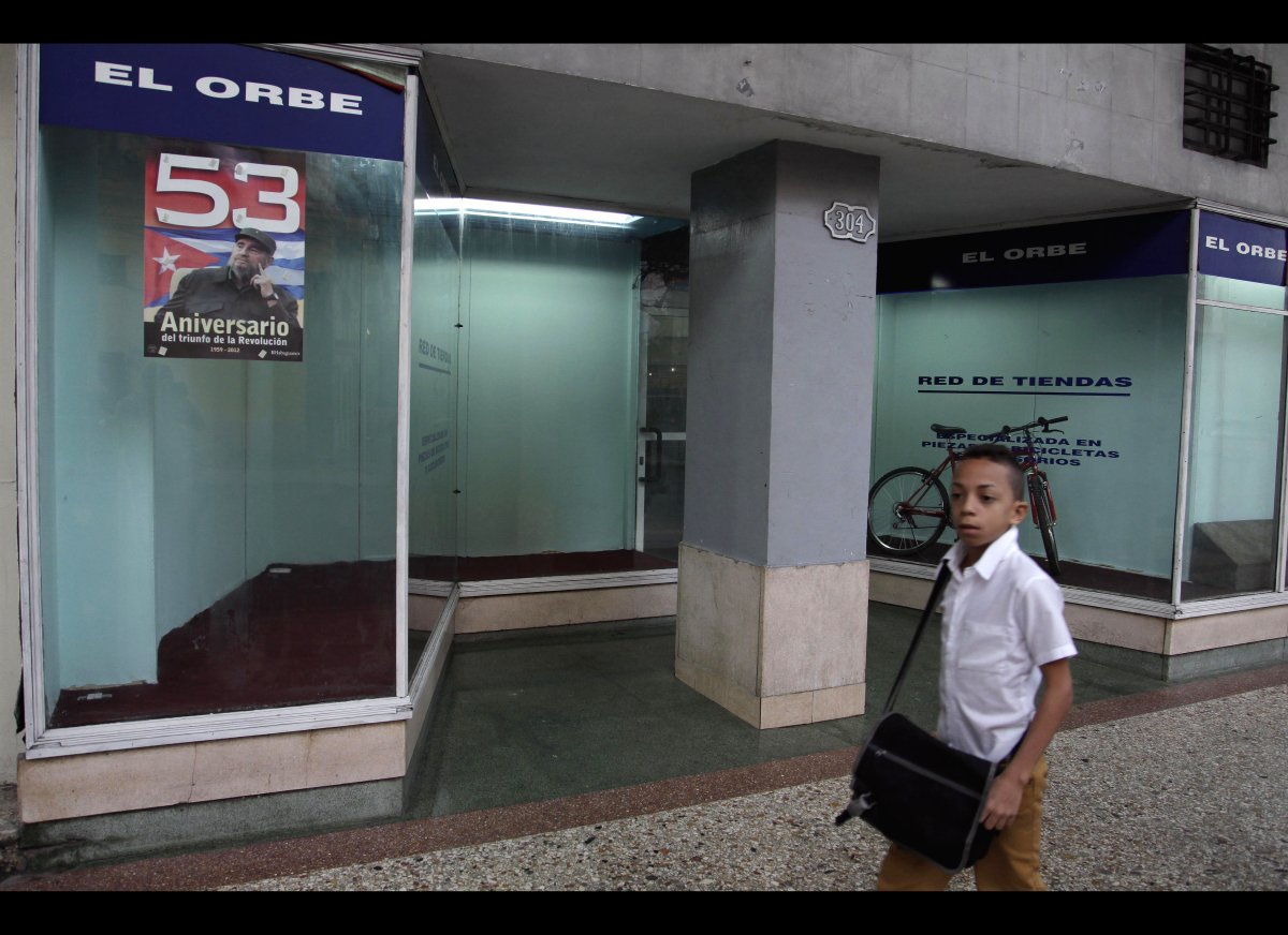 A student walks past El Orbe or The Orb bicycle shop that has a poster bearing the image of Cuba's leader Fidel Castro taped