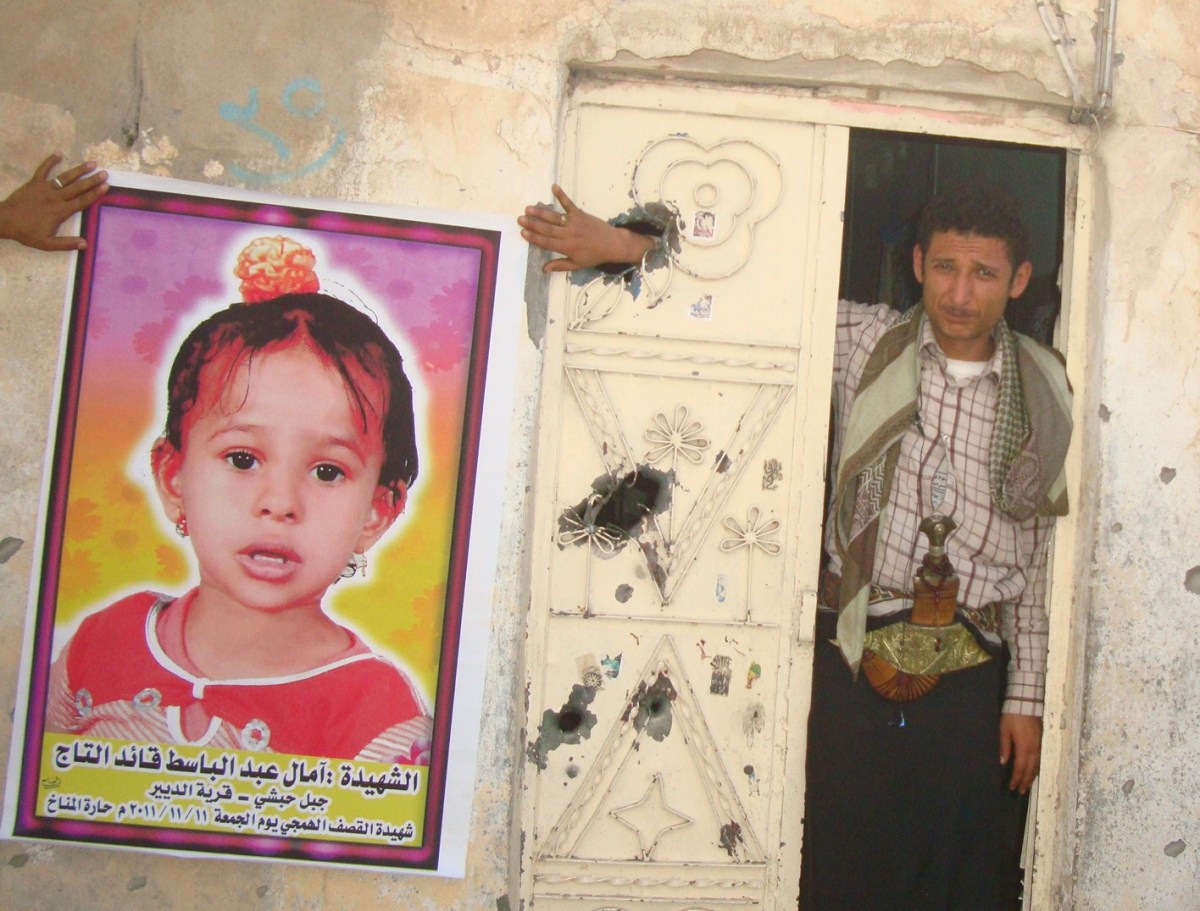 Jameel Abdullah Noman helps hold a poster of his niece Amal Adb al-Basit al-Taj, 4, who was killed by shrapnel from a shell t