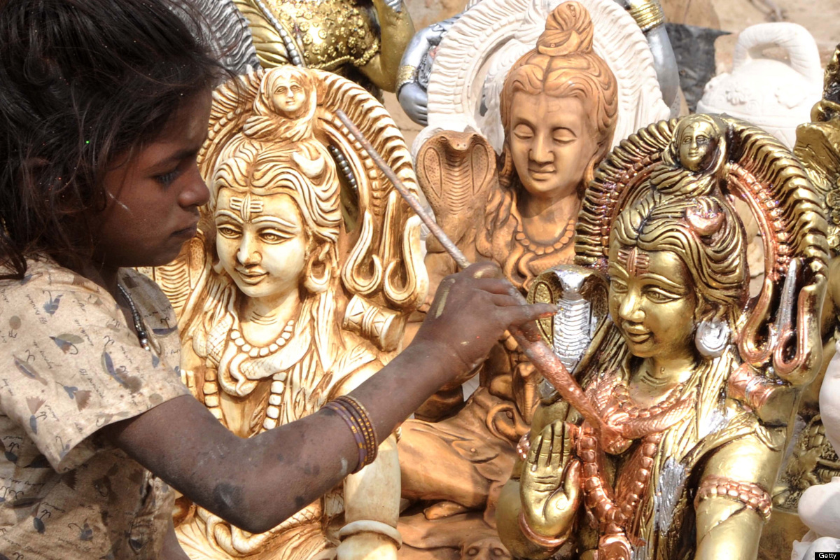 Indian girl Methi (L) gives the final touches to statues of Lord Shiva, at a roadside stall on the outskirts of Amritsar on F