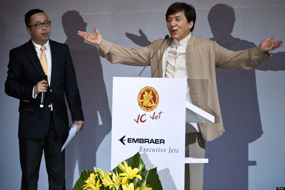 Chinese actor Jackie Chan (R) delivers a speech during the launching ceremony of the Legacy 650 executive jet, at Embraer's h