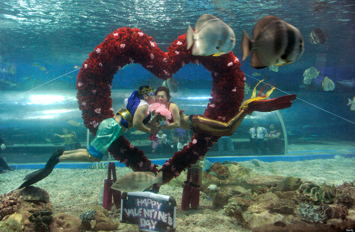 Filipino divers portraying Poseidon and a mermaid named Marina share a kiss under water surrounded by fish at Manila's Ocean