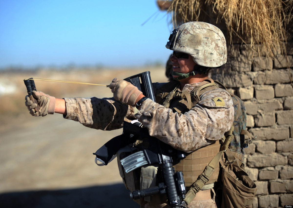 US Marine Lance Corporal Shawnee Redbear of 2nd Battalion, 1st Marines Golf Company plays with a slingshot during a patrol wi