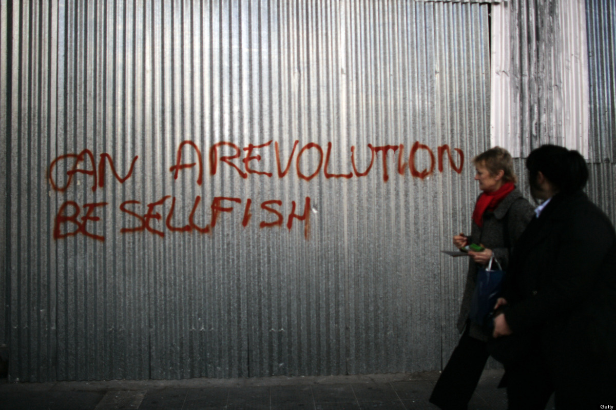 Passers by look at graffiti following violent protests which took place against the Government's austerity plans, February 13