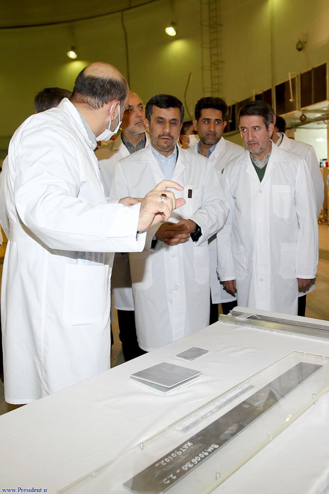 In this photo released by the Iranian President's Office, Iranian President Mahmoud Ahmadinejad, center is escorted by techni