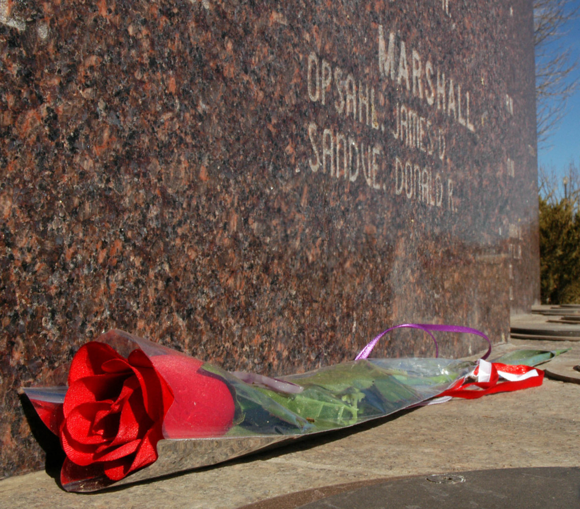 A single red rose lays at the base of a wall denoting the names of the South Dakotans who lost their lives in World War II We