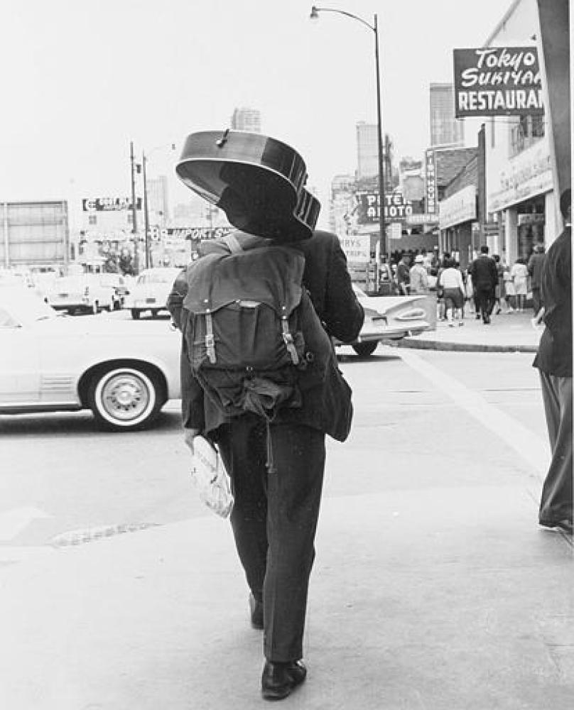 Carrying a loaf of bread, a guitar and a knapsack, a hippie walks down the street away from the Haight-Ashbury district of Sa