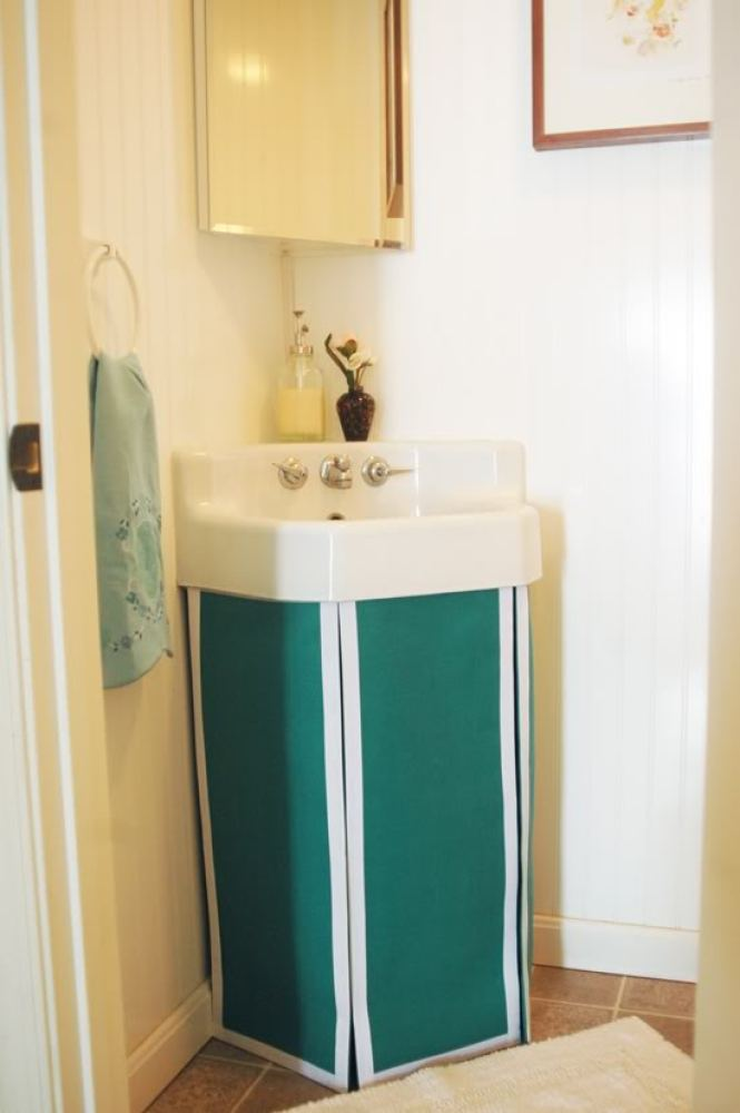 A sink skirt is a creative and affordable way to hide a trashcan or cleaning products that might look like clutter under a pe