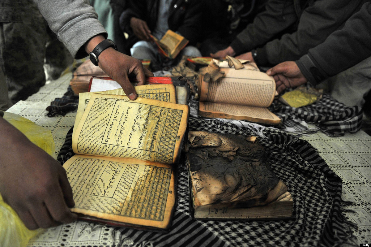 Afghan demonstrators show copies of Koran books allegedly set alight by US soldiers, during a protest against Koran desecrati