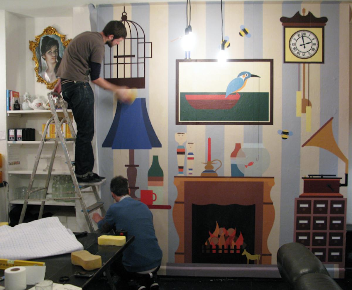 Illustrator Stephen Cheetham applies the wallpaper inside Tina, We Salute You.