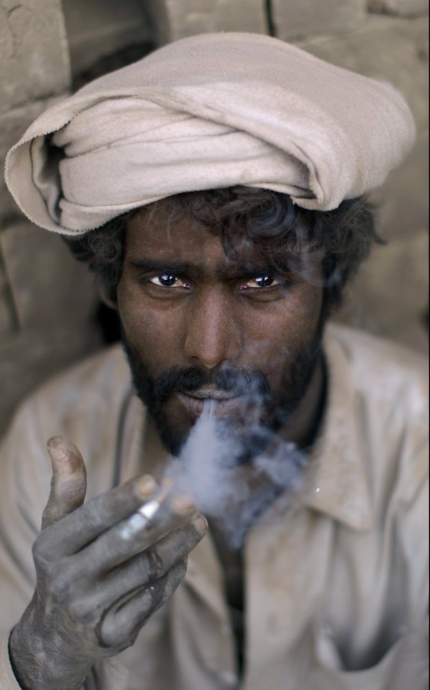 Pakistani Allah Ditta Nazar, age 35, a worker in a brick factory, smokes a cigarette while taking a break, on the outskirts o