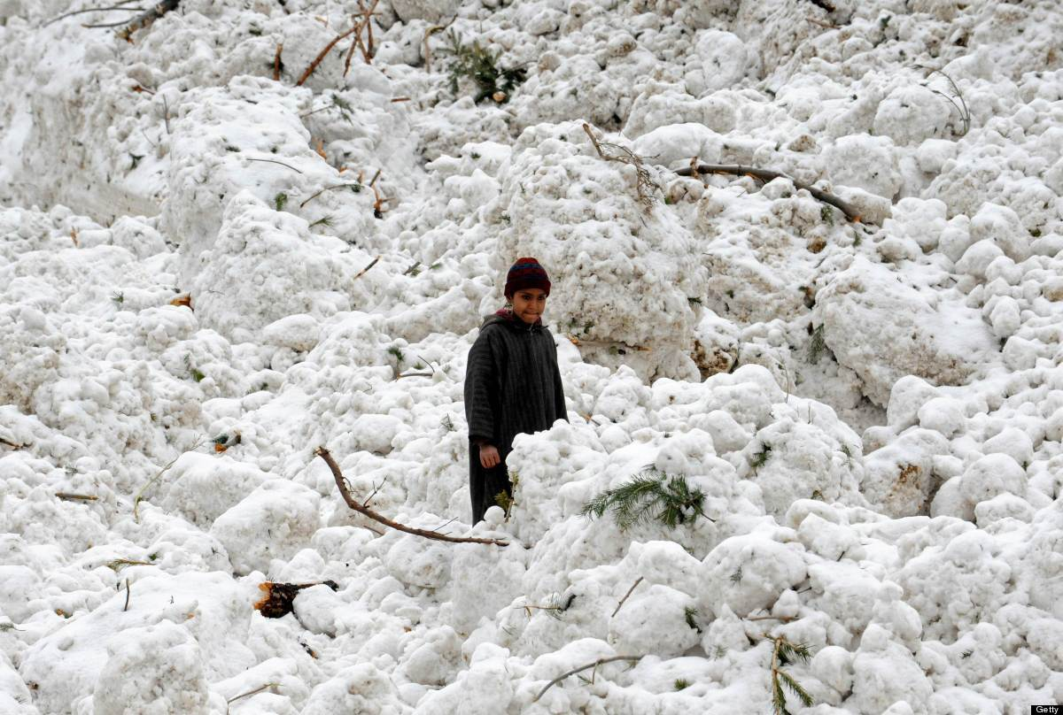 <em>From Getty:</em> A Kashmiri boy stands in snows as others search for belongings after huts were buried under snow due to