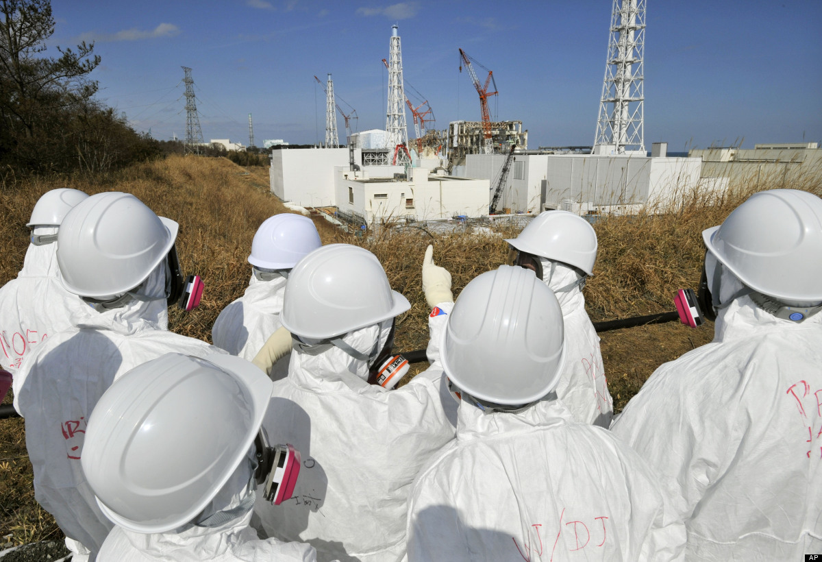 Members of the media, wearing protective suits and masks, visit the Unit 3 and Unit 4 reactor buildings of tsunami-crippled F