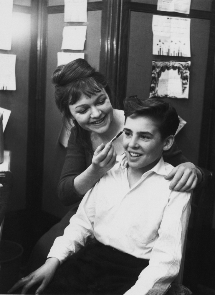 Actress Vivienne Martin helps child actor David Jones with his make-up backstage at at the New Theatre (now the Noel Coward T