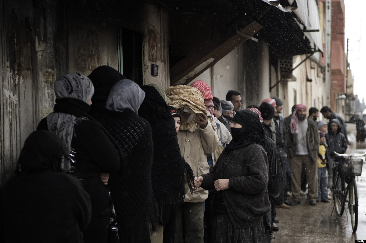 Syrians queue for bread outside a bakery in Qusayr, 15 kms (nine miles) from Homs, on March 1, 2012. Syrian rebels were still
