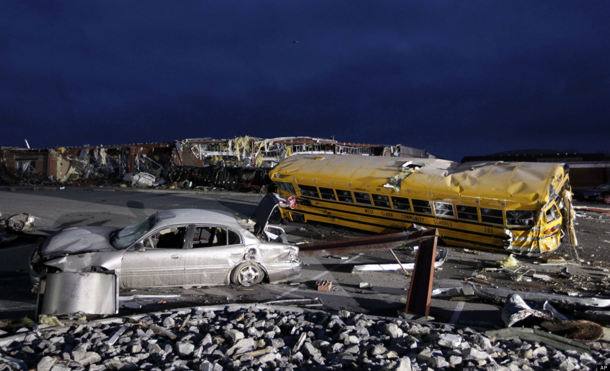 Vehicles damaged by a tornado lie in the parking lot of the Henryville Jr./Sr. High School in Henryville, Ind., Saturday, Mar
