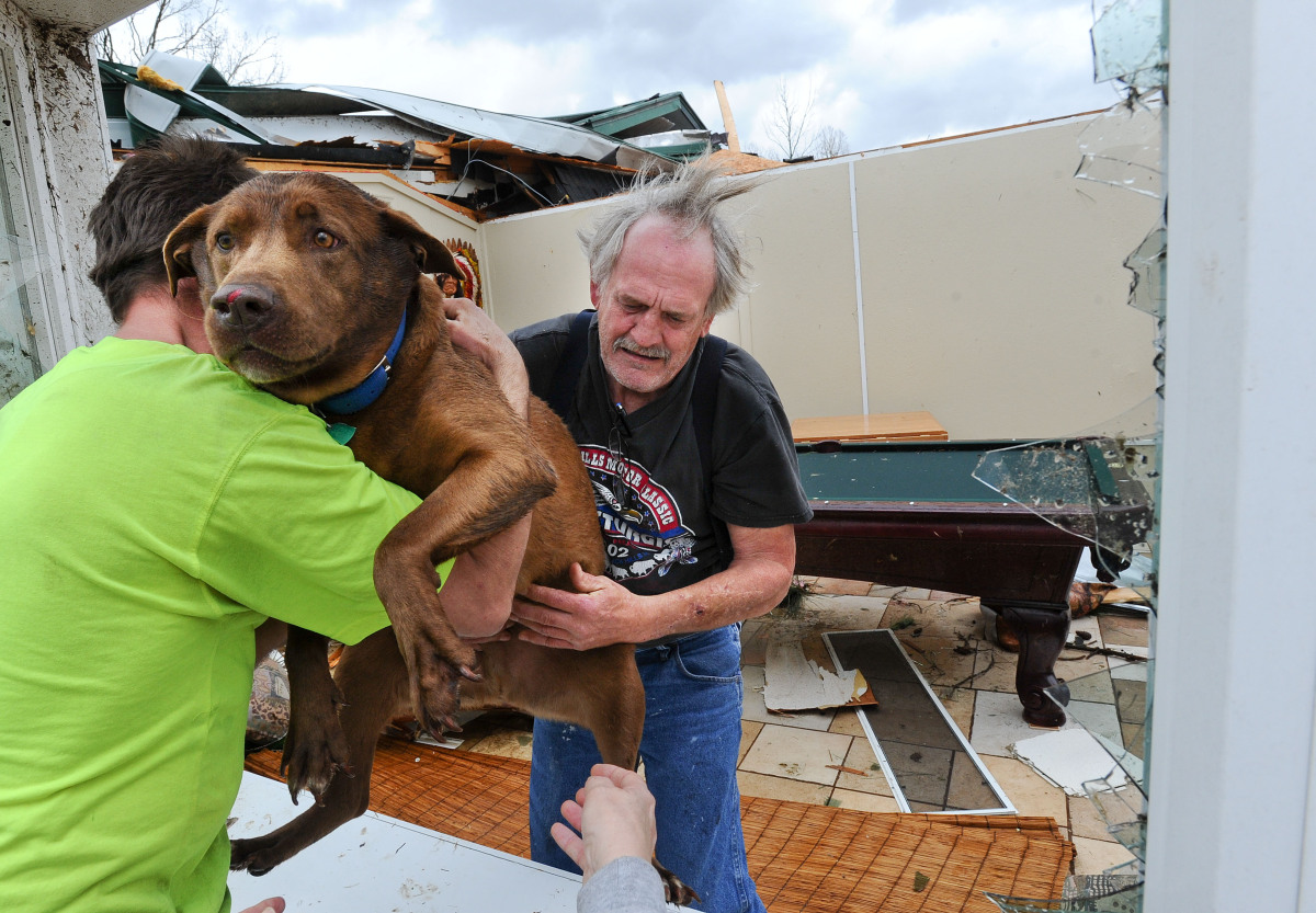 Greg Cook hands his dog Coco to Donnie Watts inside the destroyed home in Limestone County, Ala. on Friday, March 2, 2012. A