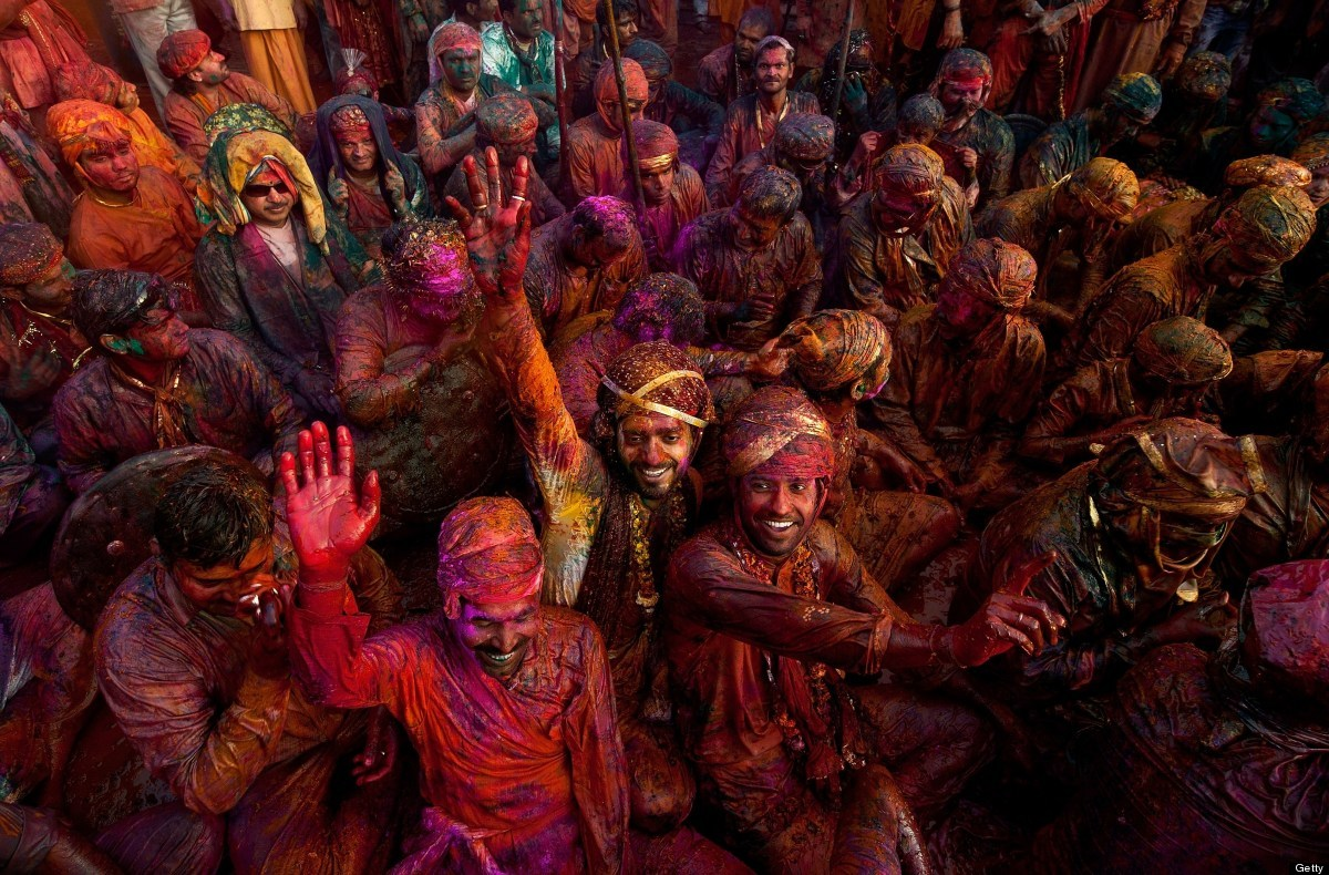 Indian villagers smear themselves with colours during the Lathmar Holi festival at the Nandji Temple in Nandgaon, some 120 km