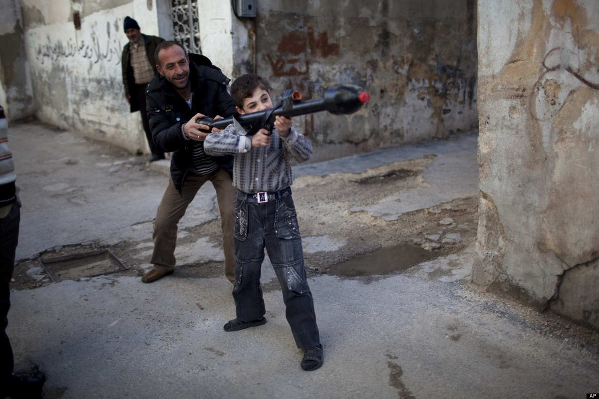 A man teaches Bilal, 11, how to use a toy rocket propelled grenade in Idlib, north Syria, Sunday, March 4, 2012. (AP Photo/Ro