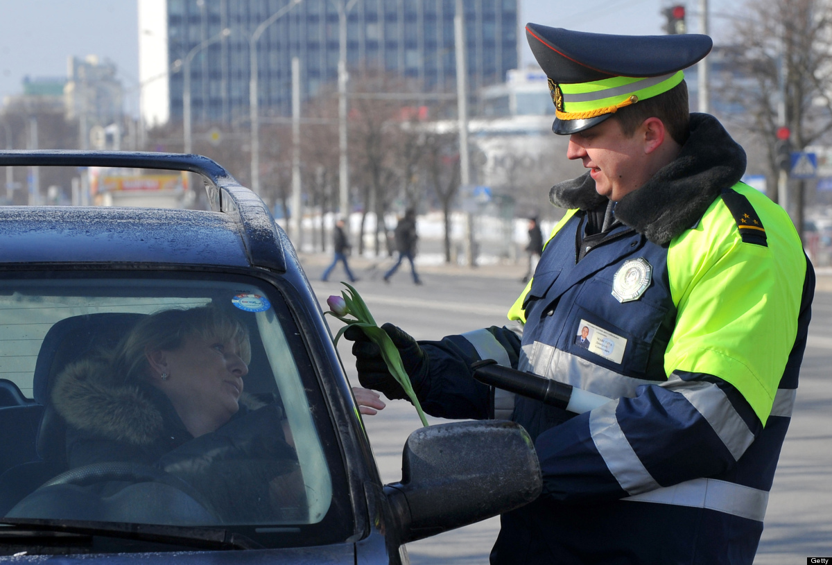 A Belarus policeman gives a flower to women driver in Minsk on March 7, 2012 a day before the International Women's Day, one