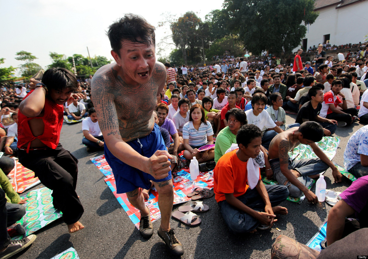 Thai devotees in a trance state race towards the statue of the founder monk at Wat Bang Phra temple.