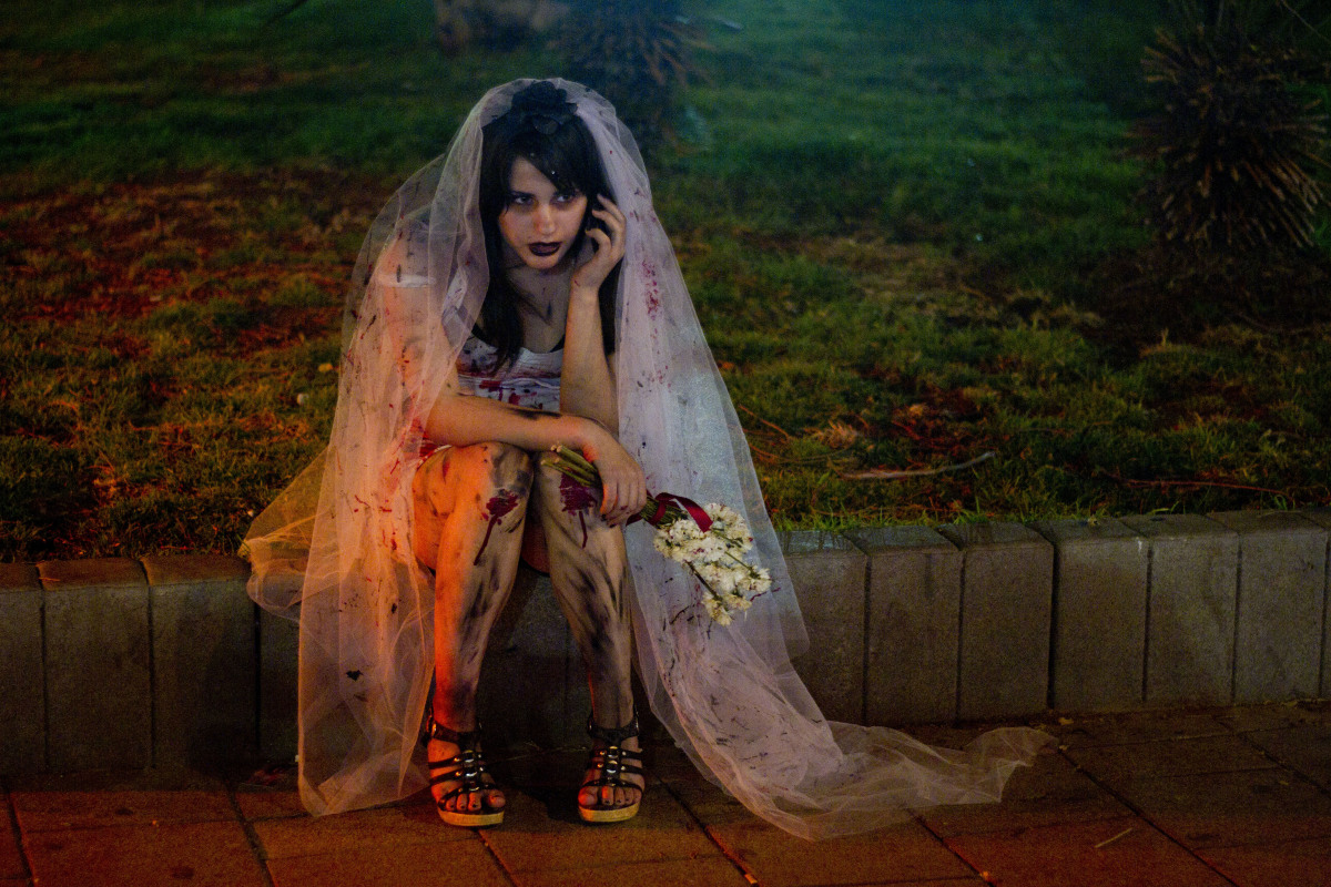 A woman wearing zombie make-up and a wedding dress sit and speaks on the phone while waiting for a friend to join the 2012 Zo