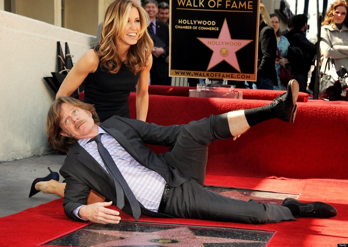 Actress Felicity Huffman laughs as her husband, actor William H. Macy (front) jokingly shows some leg as they pose on their s